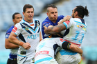 Josh Reynolds of the Bulldogs is tackled by the Titans defence. Photo / Getty Images