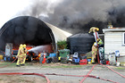 Two firefighters begin quelling the flames in a barn fire while others tap into the property's water tank. Photo / Peter Jackson
