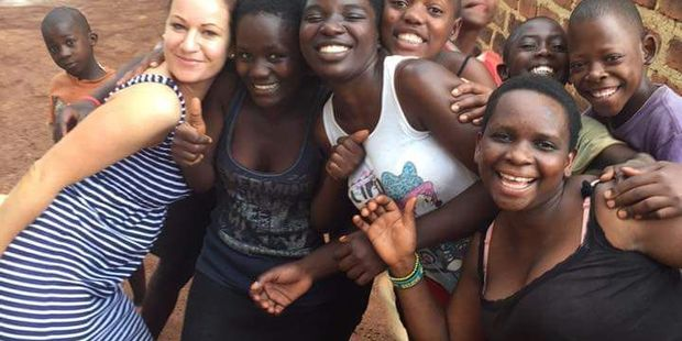 DOING GOOD: Former Chanel College student Aimee Mackey, 31, with children from the Uganda orphanage she funds through her charity Hope For Orphans International. PHOTO/SUPPLIED