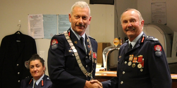 Kaeo fire chief Lindsay Murray (right) is awarded his 50-year Gold Star by United Fire Brigades Association president (and Alexandra fire chief) Russell Anderson, while Kaeo's deputy fire chief Jo Sweet-Bennett applauds. Photo / Peter de Graaf