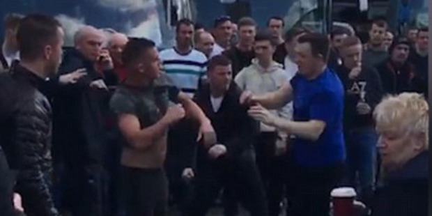The fans trade blows as the large crowd watch on with many buses parked in the background. Photo / YouTube.