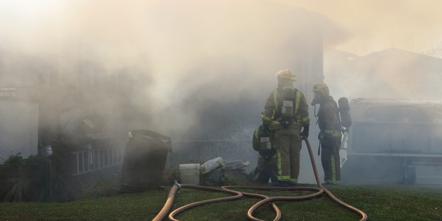 Firefighters work to put out a fire at a house in Te Puke. Photo/Pauline Carney