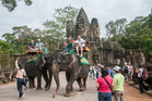 Tourists ride elephants in Angkor in Cambodia, where an elderly elephant recently suffered heart failure after working in the heat. Photo / iStock