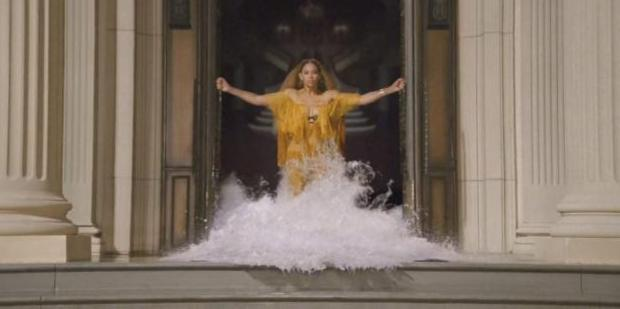 "Beyonce emerges through a wall of water pouring out of a door way in a still from Beyonce's ""Lemonade"" video."
