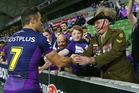 Cooper Cronk shakes the hand of a service man after the win over the Warriors. Photo / News Corp Australia