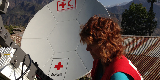 A Red Cross worker in Nepal stands before a VSAT antenna. Photo / American Red Cross