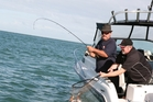 John Bebbington nets a snapper for Keith Patterson on the Kaipara Harbour. Picture / Geoff Thomas