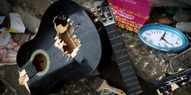 A broken guitar alongside a wall clock inside a home destroyed by the 7.8-magnitude earthquake, in Pedernales, Ecuador. Photo / AP