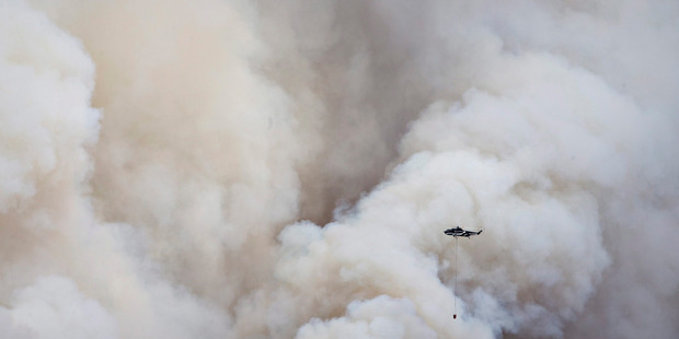 A helicopter battles a bushfire in Fort McMurray Alberta. Photo / AP