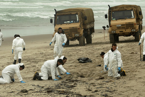 Soldiers pick up clumps of oil off Papamoa Beach this morning as the oil spill from the container ship Rena continues to wash up on Bay of Plenty beaches. Photo / Alan Gibson