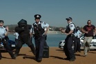 Australian Federal Police get down feat. a man in a full bomb suit. Photo / AFP