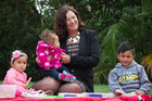 Labour MP Sue Moroney sits with ... who joined others for a protest picnic at Alberton Reserve in Parnell where they made a giant Mother's Day card for Prime Minister John Key. Photo / Greg Bowker