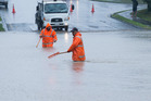Porirua City Council workers attempting to clear floodwaters from Warspite Avenue after heavy rain hit the Wellington region. Photo / Mark Mitchell