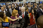 Warren Buffett, chairman and chief executive officer of Berkshire Hathaway Inc., center, speaks with members of the media as he tours the exhibition floor. Photo / AP