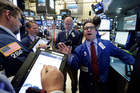 Specialist Paul Cosentino, right, works with traders at his post on the floor of the New York Stock Exchange. Photo / AP