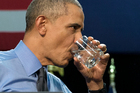 President Barack Obama drinks water as he finishes speaking at Flint Northwestern High School. Photo / AP