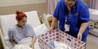 Keyshla Rivera smiles at her newborn son in a baby box in a Philadelphia hospital. Photo / AP