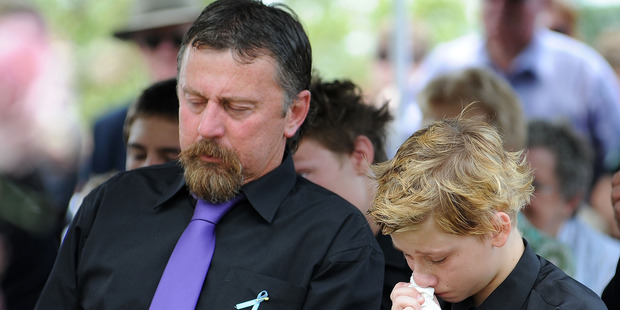 John Tyson sits next to his son Blake Tyson as they mourn at the funeral of family members Donna Maree Rice and son Jordan Rice. Photo / Getty Images