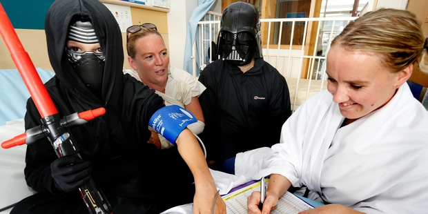 Patient Tamati Caldwell (left), mum Karen, Dr Andre Schultz (Darth Vader) and nurse educator Brydy Wilson use the force to get the 9-year-old through a scary injection at Whangarei Hospital. Photo / John Stone