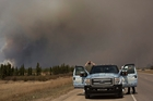 Residents of Fort McMurray escaped the blaze, some stopping to take photos. Pictures / AP