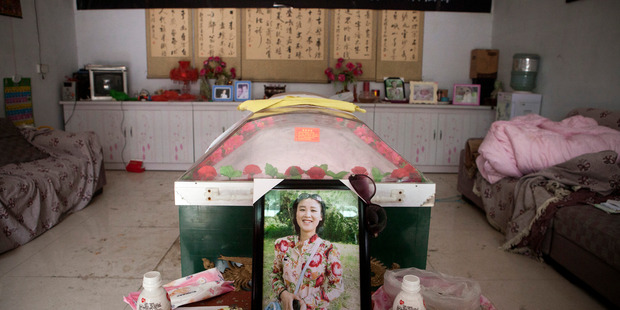 A picture of the victim Li Hongxia, and the refrigerator coffin where her dead body lies. Photo / Washington Post