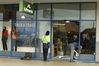People work to clean up the mess left behind from a ram raid at a Kathmandu store in Fraser Cove Shopping Centre. Photo / John Borren