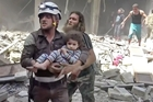 A civil defence worker carries a child wounded by an airstrike in Aleppo on Friday as rescuers comb the ruins. Photo / AP