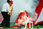 Security staff extinguish a flare during the 2015/16 A-League Grand Final. Photo / Getty