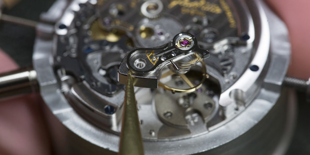 A watchmaker prepares to position an escapement wheel during the assembly of a Senator Chronograph Panorama Date luxury wristwatch. Photo / Bloomberg