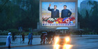 Pedestrians pass by one of many scenes of the late Kim Il Sung and his son Kim Jong Il in Pyongyang. This week, the ruling Workers' Party will hold its seventh congress. Photo / Linda Davidson