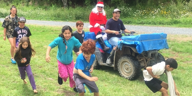 The kids scramble for lollies as Hana Koko (Santa Claus) arrives at the Forest Pools opening by quad bike.