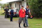 A youth, one of three arrests on Moerewa's Leatty St yesterday, is marched to a waiting police car after removing two sweatshirts bearing Mongrel Mob insignia.