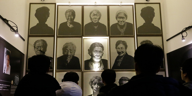 """South Korea high school students look at portraits of late former """"sex slaves"""" who were forced to serve for the Japanese Army during World War II. AP photo / Ahn Young-joon"""
