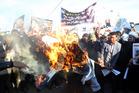 Followers of Shiite cleric Muqtada al-Sadr burn an effigy of King Salman of Saudi Arabia as they hold posters of Sheik Nimr al-Nimr and Shiite cleric Muqtada al-Sadr. AP photo / Khalid Mohammed
