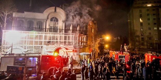 Smoke rises as Iranian protesters set fire to the Saudi embassy in Tehran. Photo / AP