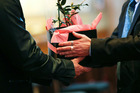 A family member of an organ/tissue donor receives a camellia plant from a donor co-ordinator during a remembrance service for organ donors in Wellington. Photo / Hagen Hopkins