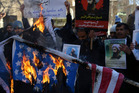 Iranian demonstrators burn representations of the US and Israeli flags during a demonstration in front of the Saudi Arabian Embassy in Tehran, Iran. Photo / AP
