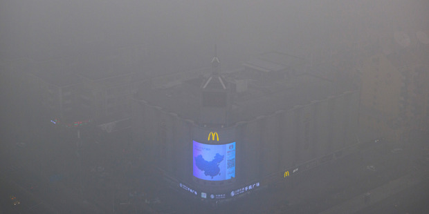 A video display on the side of a building shows a map of China amid heavy pollution and fog in Beijing. Photo / AP