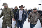 Ammon Bundy, center, one of the sons of Nevada rancher Cliven Bundy, walks off after speaking with reporters. Photo / AP