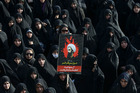 An Iranian woman holds up a poster showing Sheikh Nimr al-Nimr in Tehran. Photo / AP