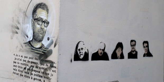 A painting of killed cartoonists Charb , left, and Honore, Wolinski, Cabu, Charb and Tignous seen on a wall outside Charlie Hebdo former office, one year after the attacks. Photo / AP