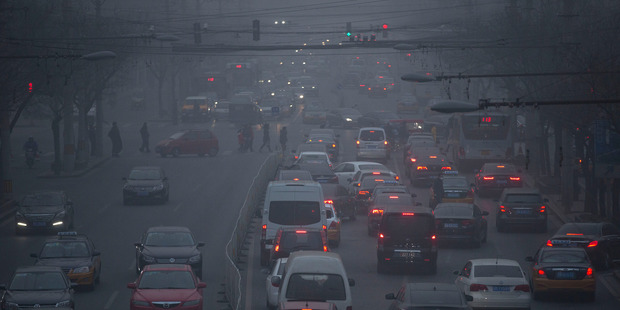 Pedestrians make their way across a busy intersection on a day with severe air pollution in Beijing. Photo / AP