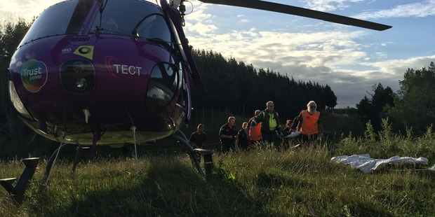 Paramedics and Land Search & Rescue volunteers help carry a 17-year-old girl scout to the Tauranga Trustpower TECT Rescue Helicopter in the Kaimai Range. Photo/supplied