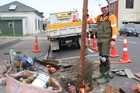 Braedyn Duff in the drain and Hayden Feierabend spent most of Tuesday clearing a rubbish-clogged underground drain on Allardice St, which had flooded during last Thursday's downpour. Photo / Christine McKay