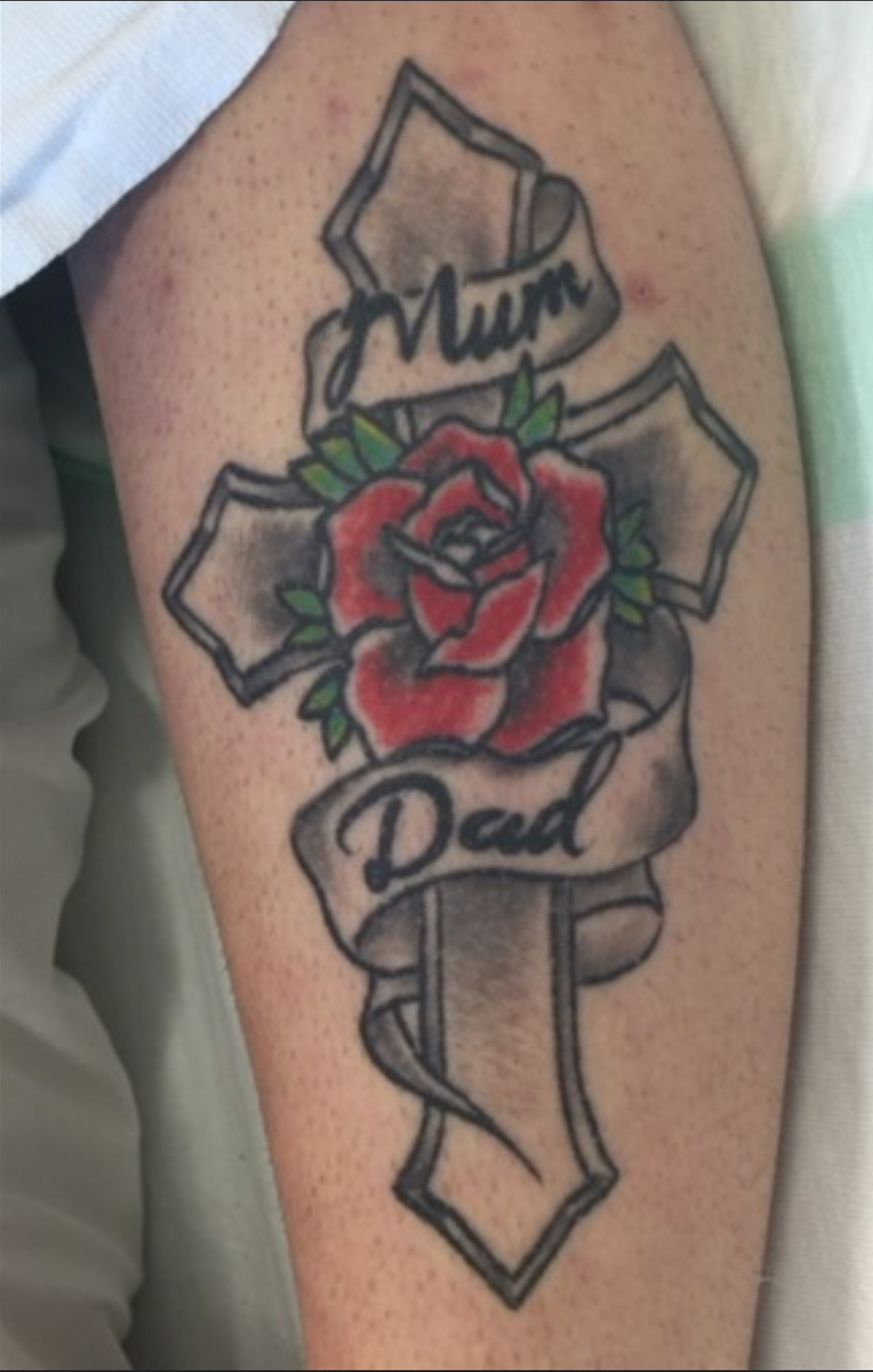 The woman has a tattoo of a cross with a rose, and has the words 'mum' and 'dad'. Photo / Supplied