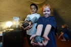 Tion Tite and Maddison Thomas show off meteorites they learned about in the portable Starlab. Photo / George Novak