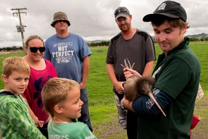 DOC ranger Dan Arnold with one of the released kiwi and locals.