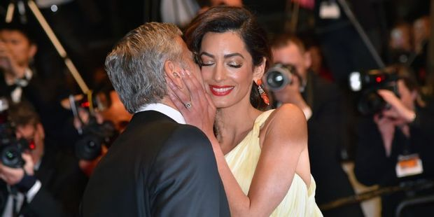US actor George Clooney kisses his wife, British-Lebanese lawyer Amal Clooney. Photo / AFP