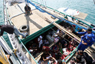 Iranian asylum seekers who were caught in Indonesian waters while sailing to Australia sit on a boat at Benoa port in Bali, Indonesia. AP file photo, 2013 / Firdia Lisnawati