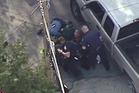 This aerial image made from a helicopter video provided by WHDH shows several officers hitting Richard Simone, who had exited his vehicle after a high-speed police pursuit. Photo / AP